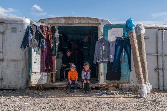 Boys sitting on the edge of bazaar shop in Murghab
