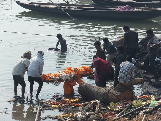 A body being  bathed in the Ganges while someone pans for gold in the background