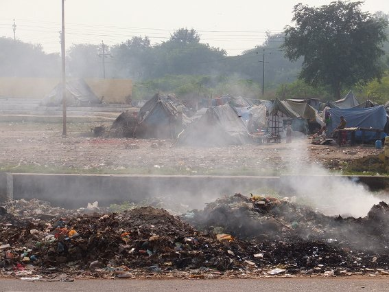 Piles of burning garbage in front of a shanty town outside the Agra Fort