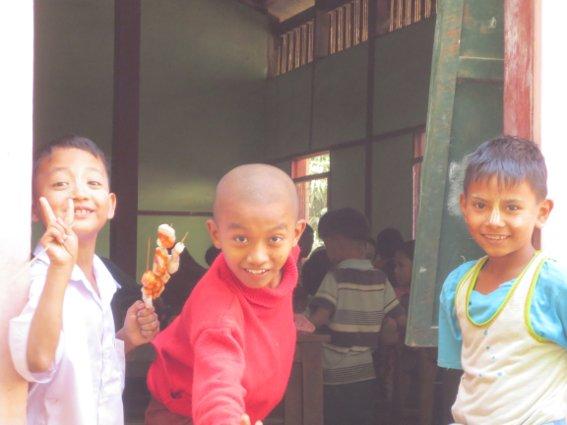 Three boys, the one on the right has thanaka on